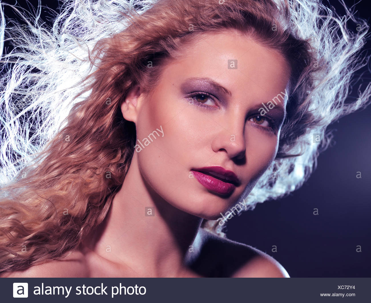 Portrait of a woman wearing makeup with flying long hair - Stock Image
