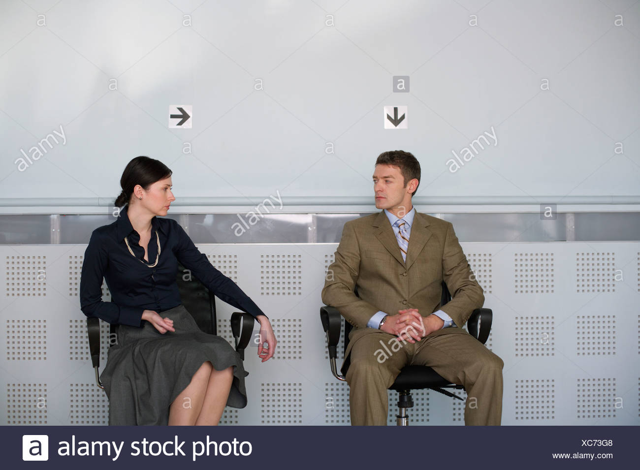 Business couple sitting on chairs - Stock Image