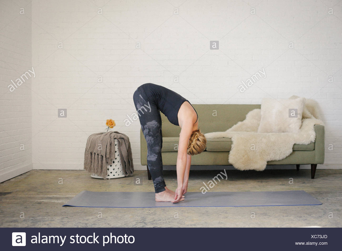 A blonde woman standing on a yoga mat in a room, doing yoga, bending down, touching her toes with her hands. - Stock Image