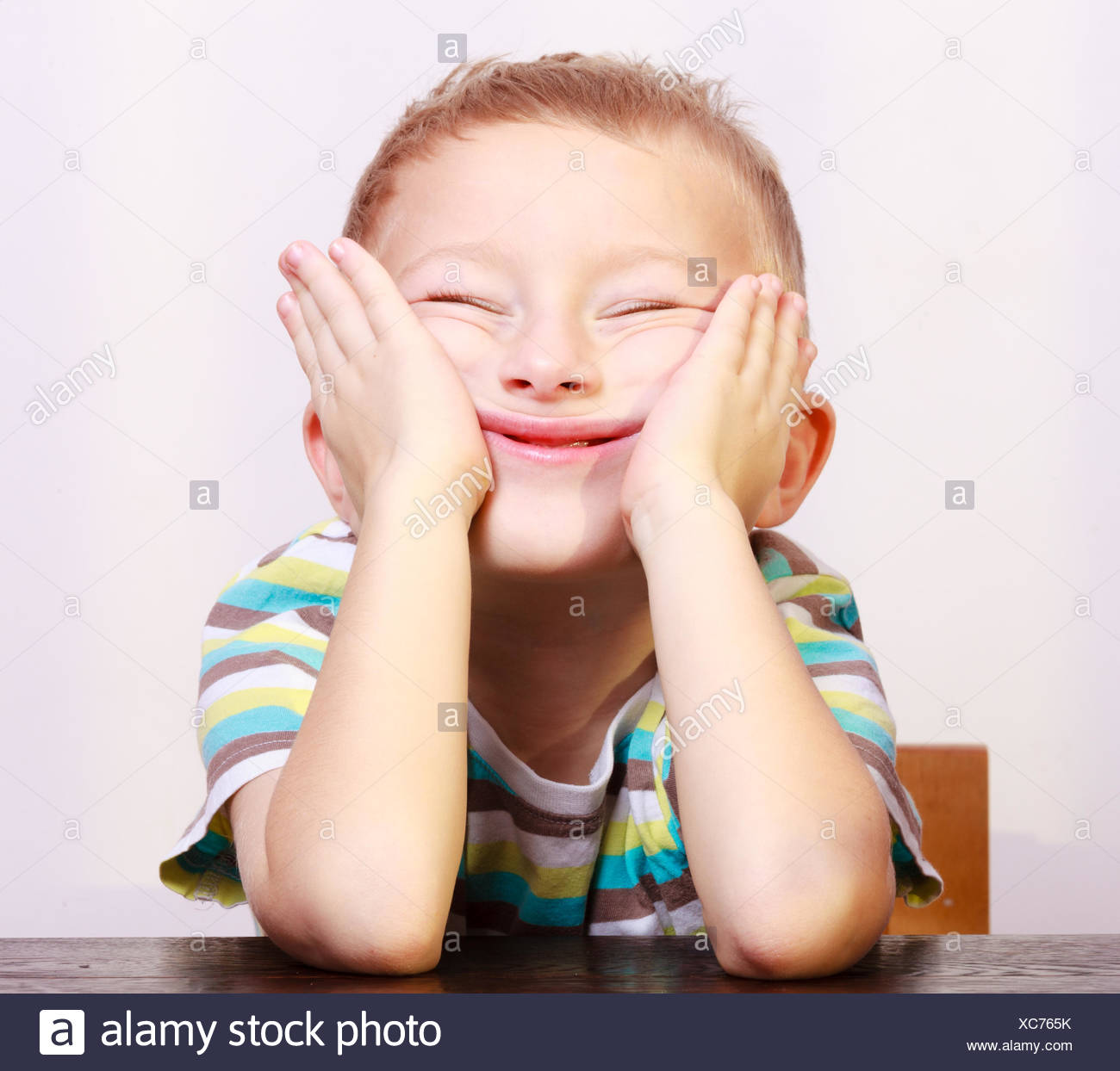 1fcff6ed5 Portrait of blond boy child kid making funny face at the table Stock ...
