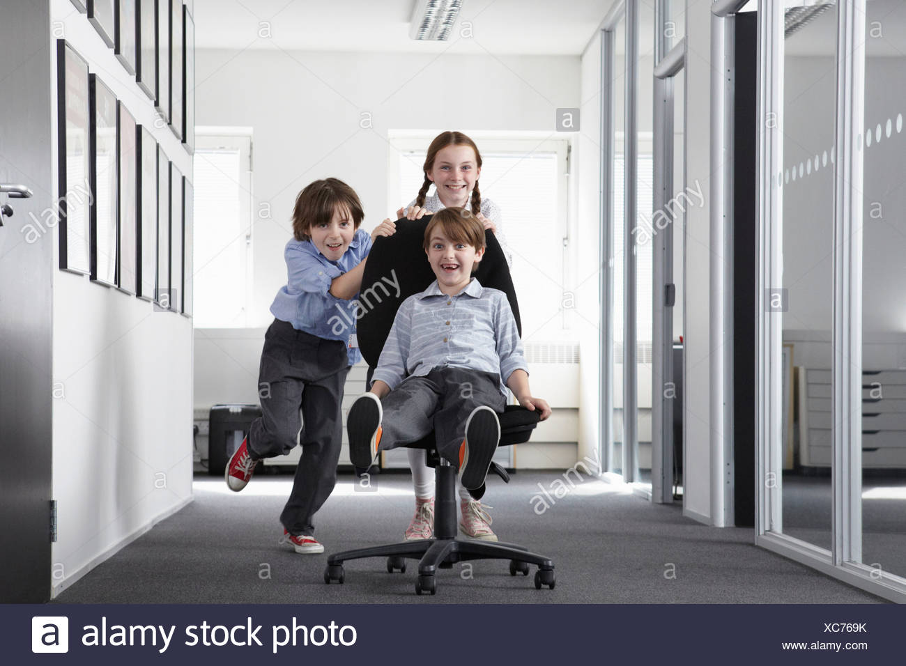 Three children playing in office corridor on office chair - Stock Image
