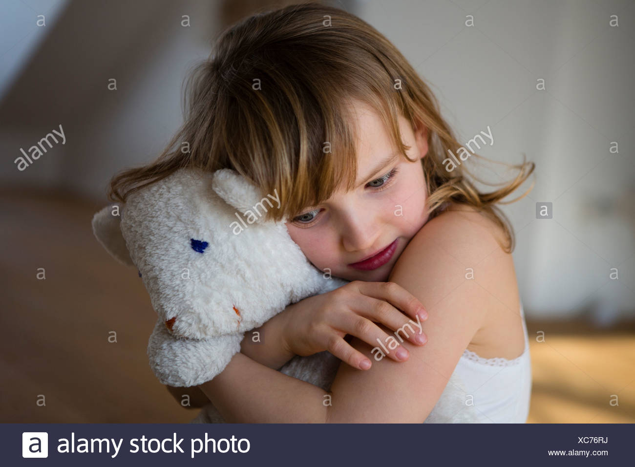 Distressed girl holding onto teddy bear - Stock Image