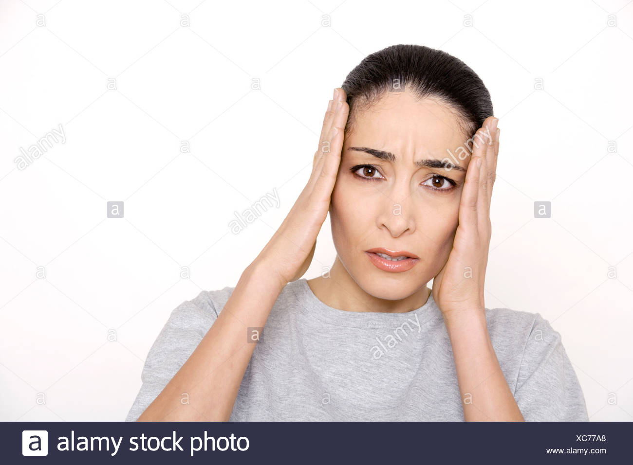 Young woman with hands on head, portrait - Stock Image
