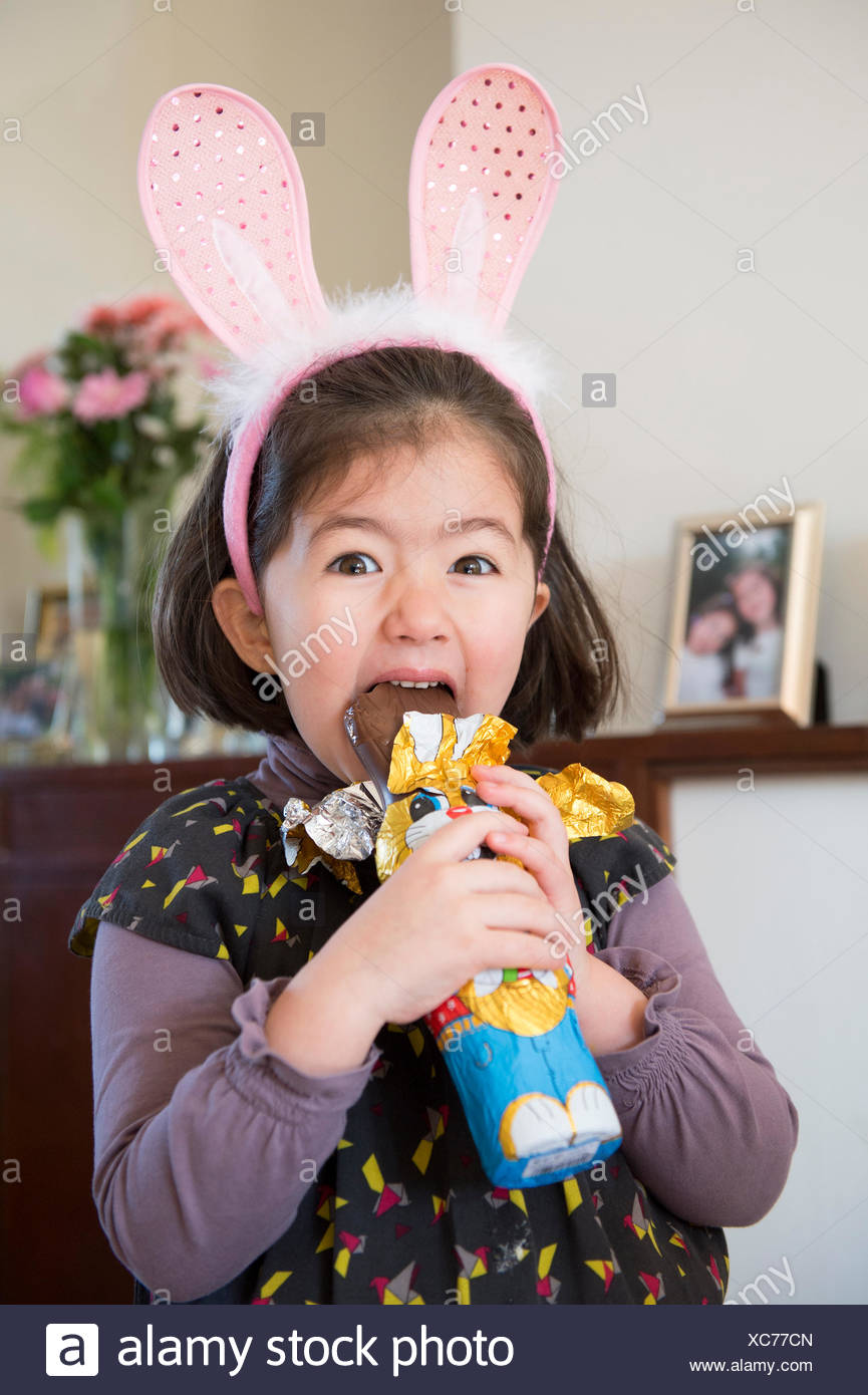 Young girl wearing bunny ears, just about to bite into chocolate bunny - Stock Image