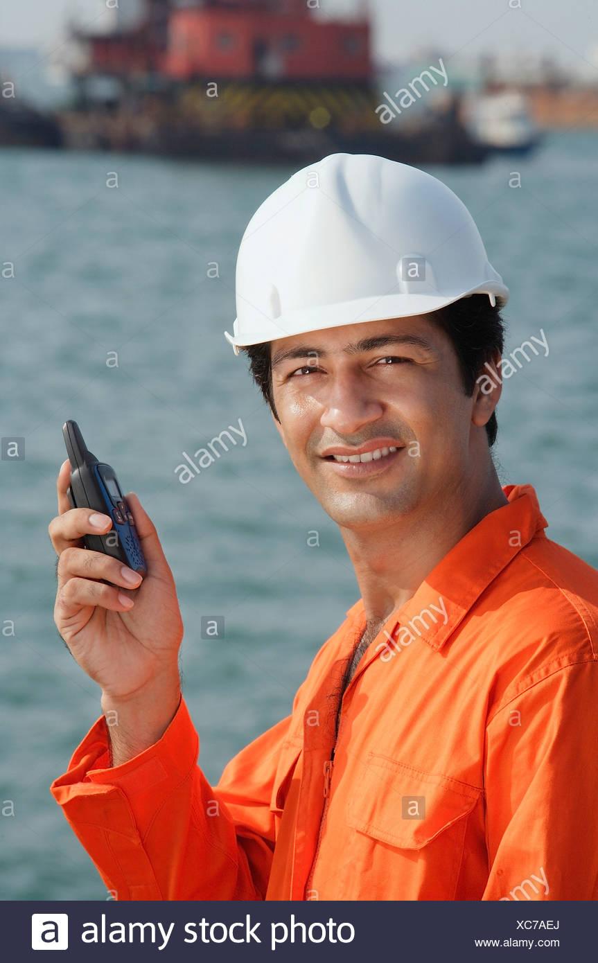 Man in work uniform smiling at camera - Stock Image
