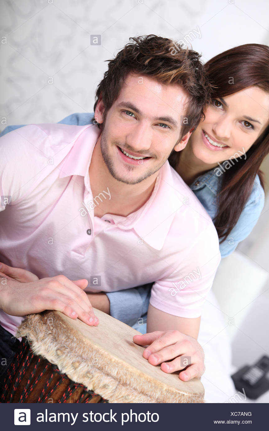 young couple all smiles with djembe drum - Stock Image