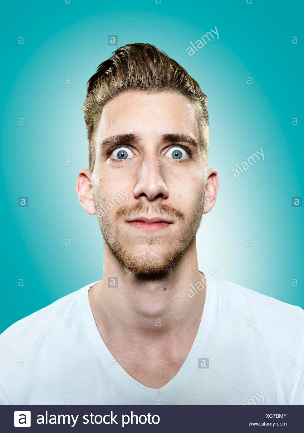 Portrait of young man with eyes wide open, studio shot - Stock Image