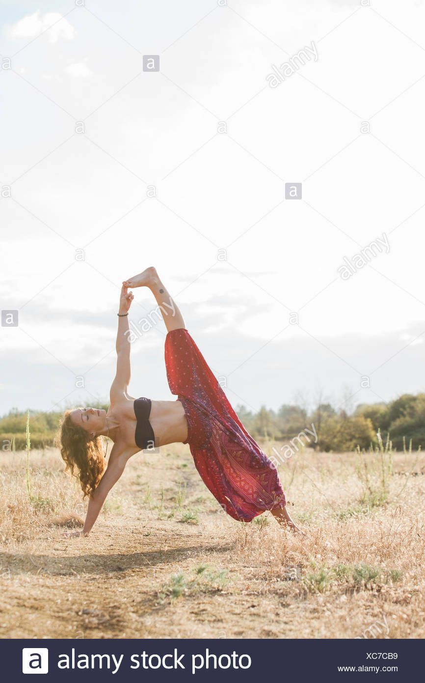 Boho woman in extended side plank yoga pose in sunny rural field - Stock Image