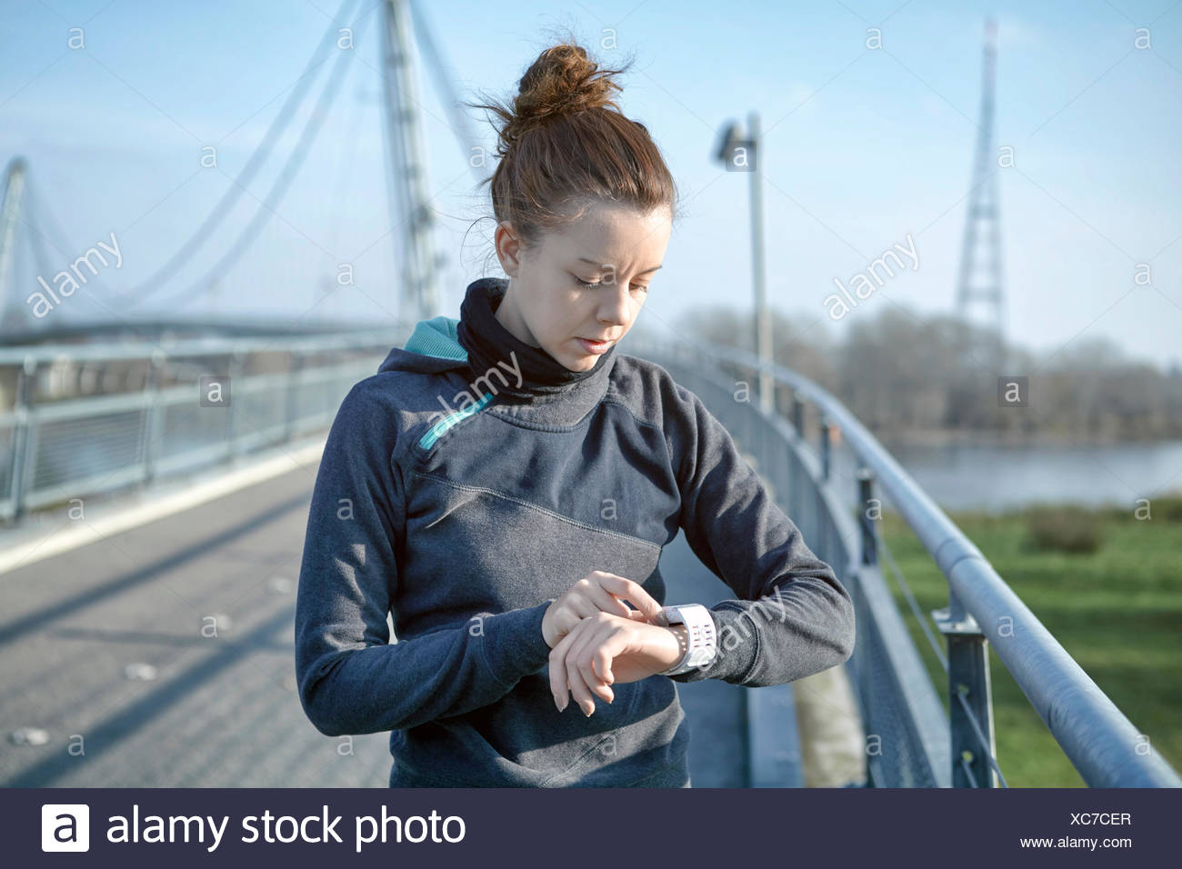 Young woman checking heart rate monitor after jogging - Stock Image