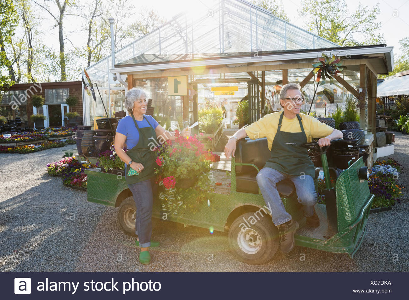 Workers with hanging flower basket in cart outside greenhouse - Stock Image