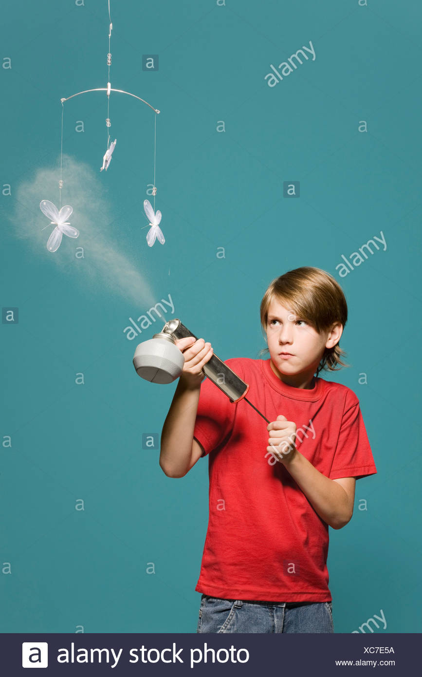 Boy spraying butterfly mobile with insecticide - Stock Image