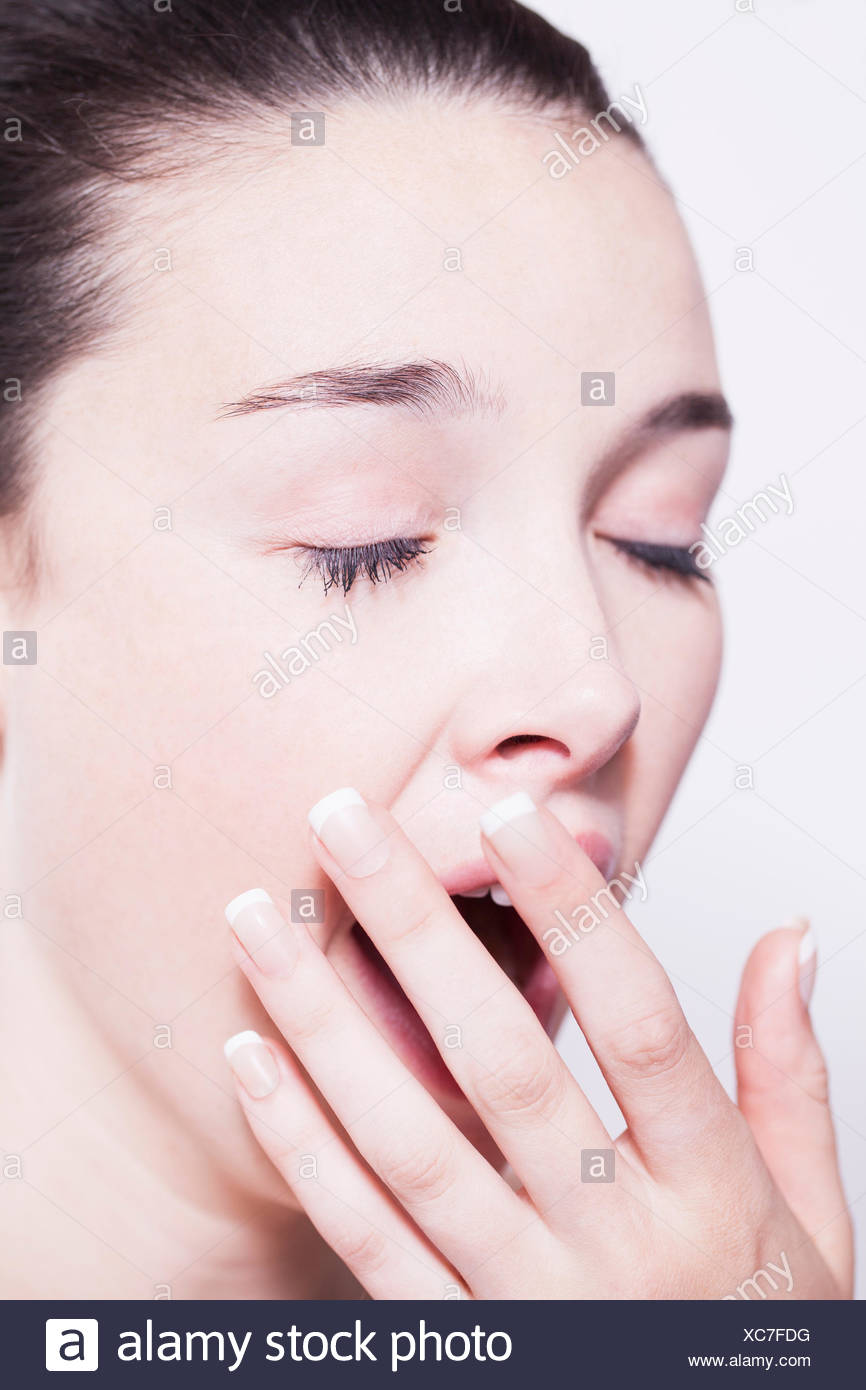 Head shot of young woman yawning - Stock Image