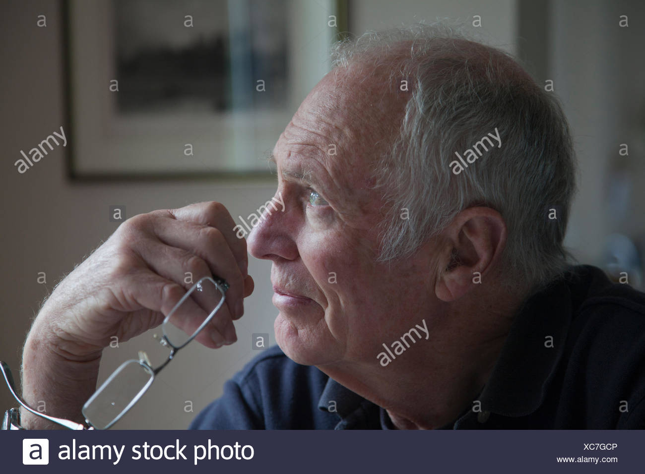 Senior man, holding eyeglasses, looking out of window - Stock Image