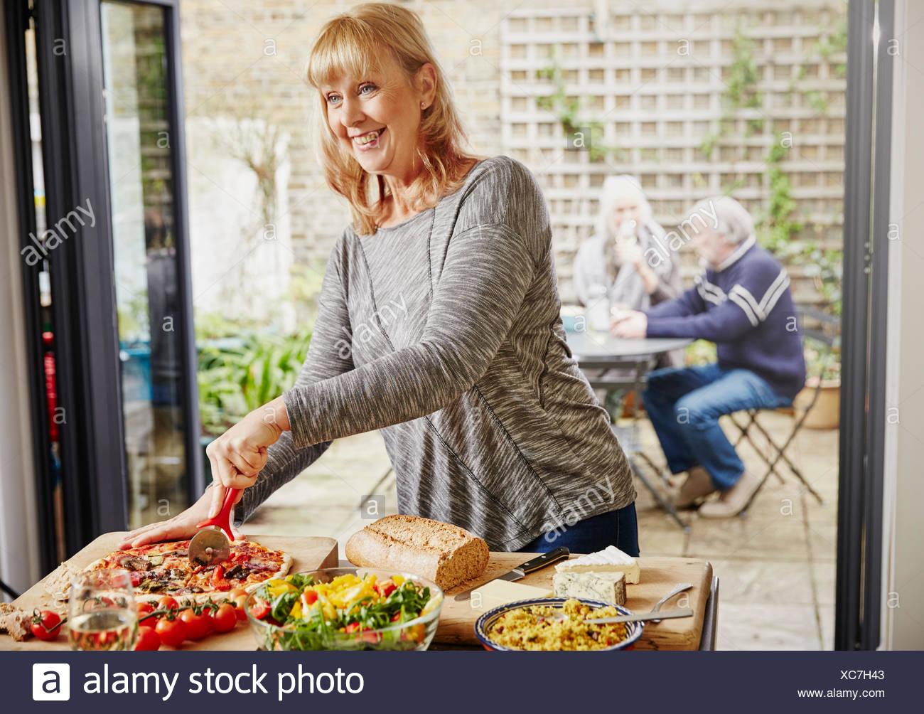 Mature woman cutting pizza - Stock Image
