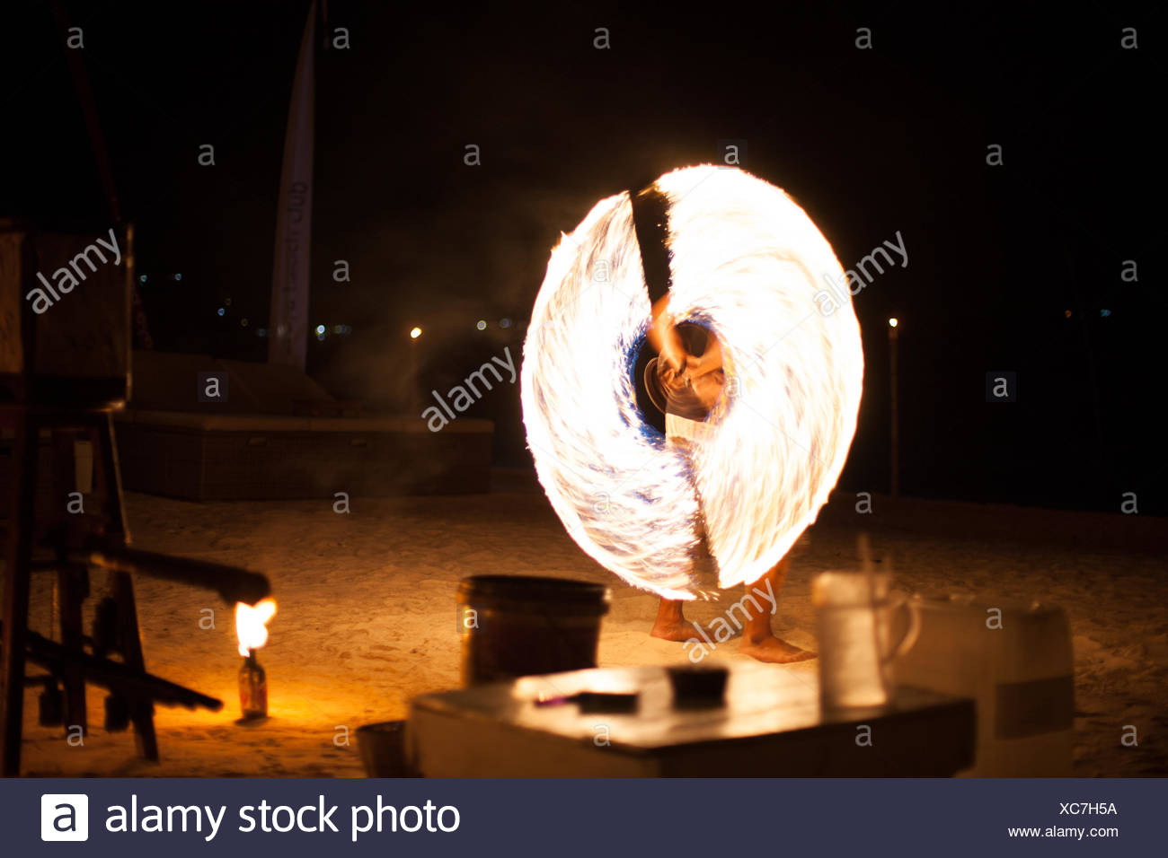 Man Doing Fire-Twirling Performance At Night - Stock Image