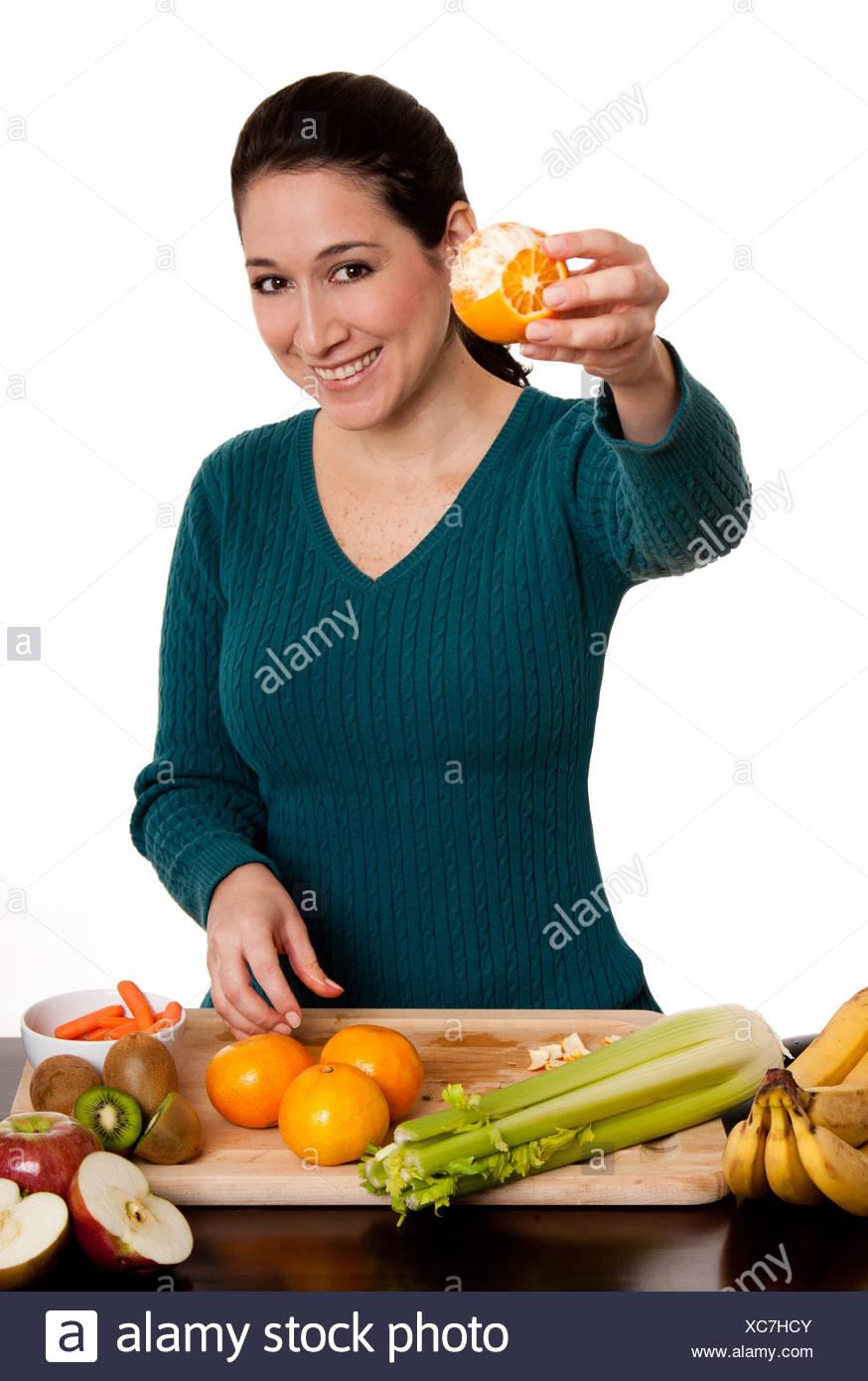 Woman presenting peeled ornage fruit - Stock Image