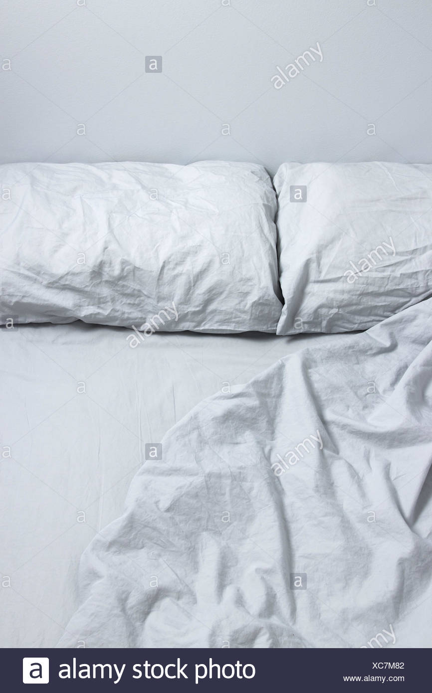 Messy bed with gray bedclothes - Stock Image