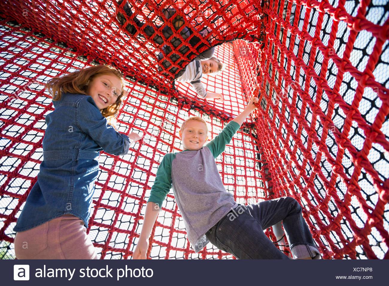 Portrait kids climbing rope net at playground - Stock Image