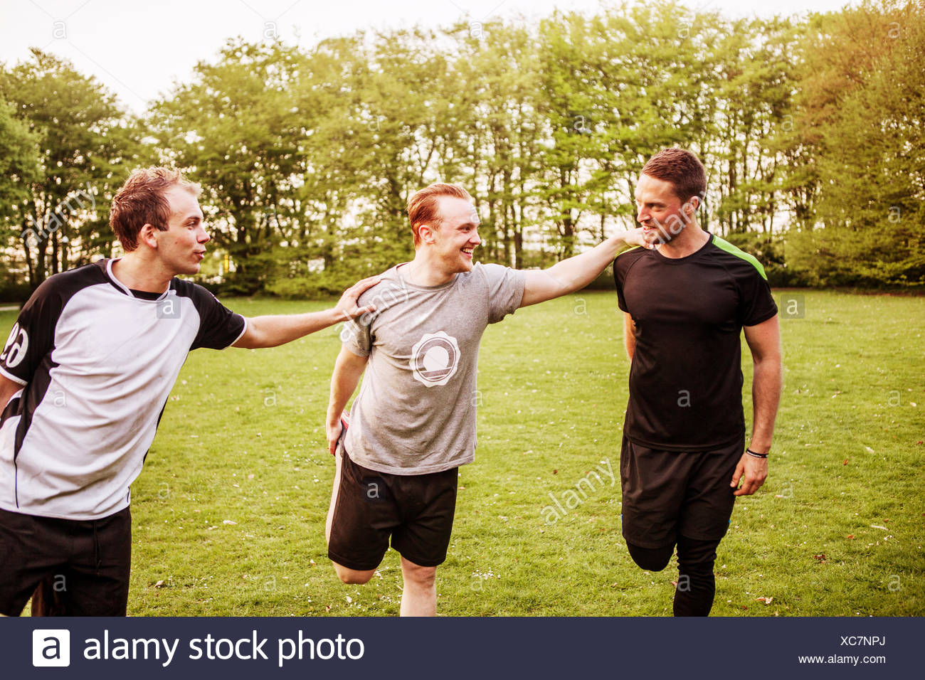 Happy friends standing on one leg while exercising at field - Stock Image