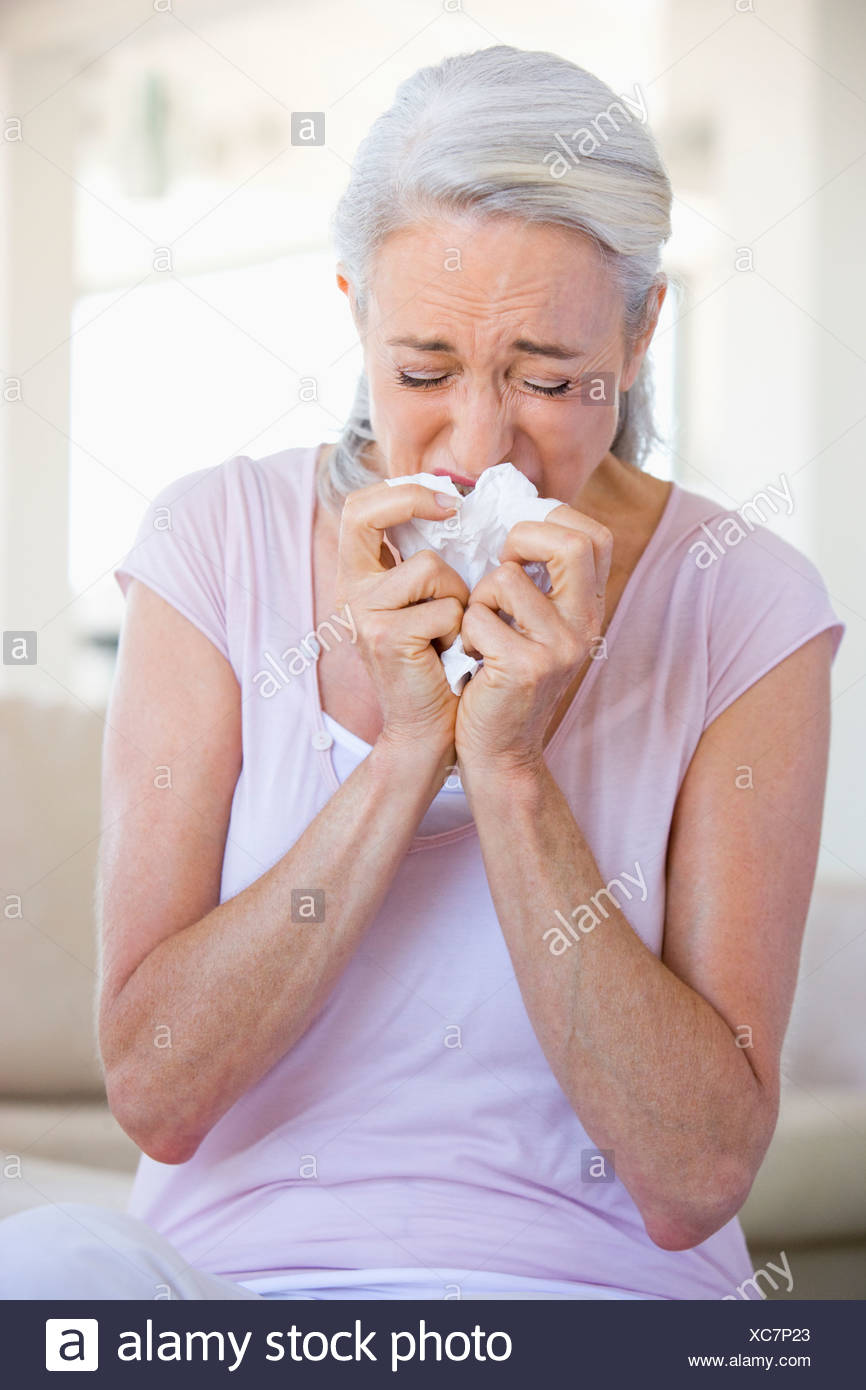 Woman Blowing Her Nose - Stock Image