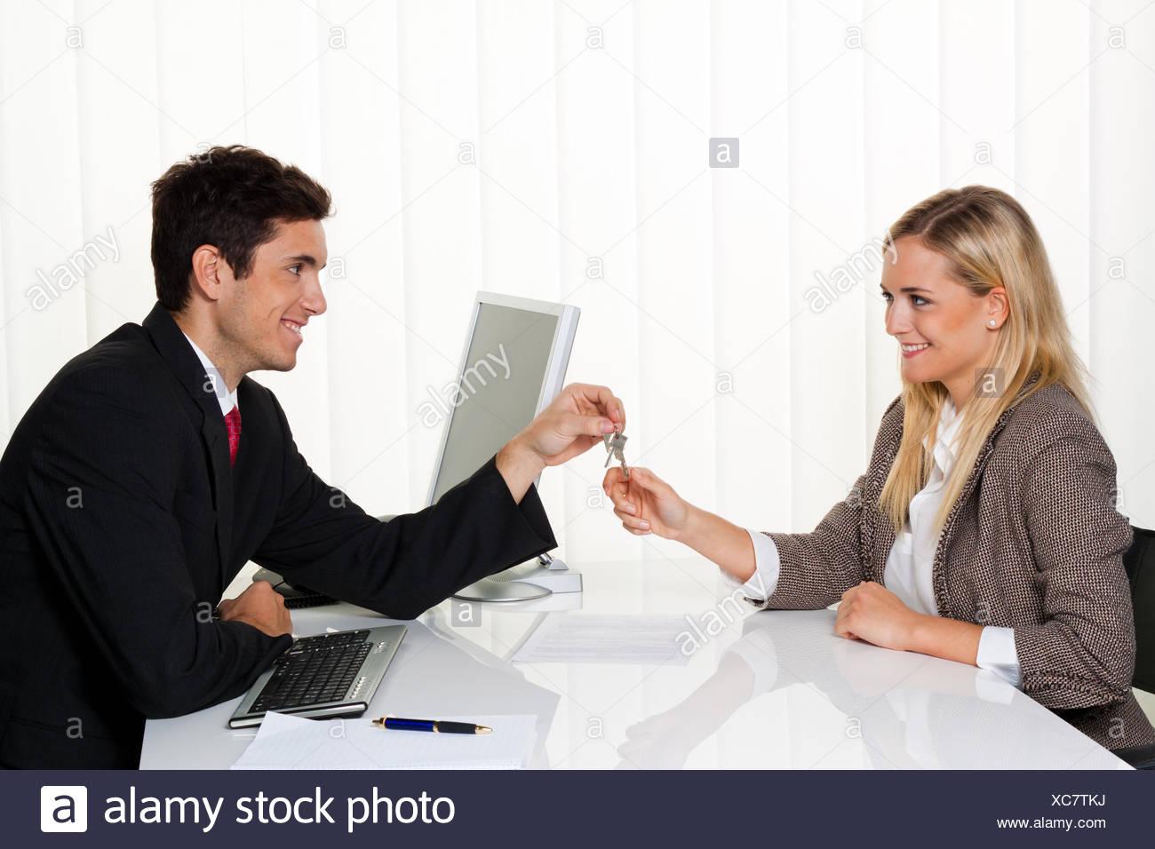Brokers and tenants make rental agreement. Handover - Stock Image