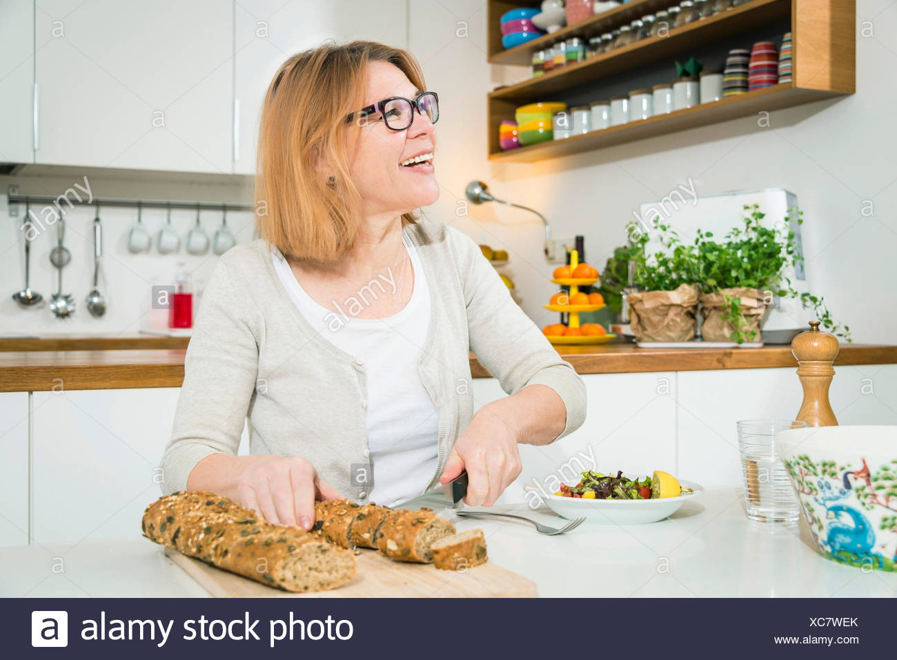 Senior woman cutting bread - Stock Image