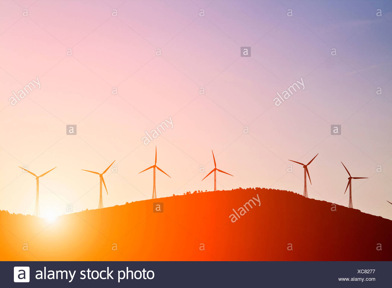 Silhouette of windmills on rural hills - Stock Image