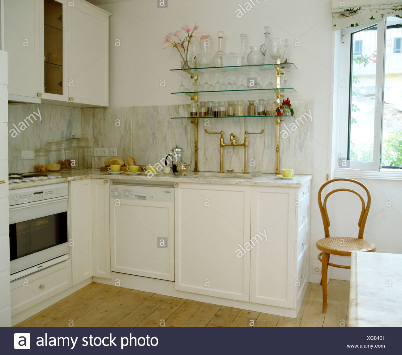 Glassware on glass shelves in white coastal kitchen with ...