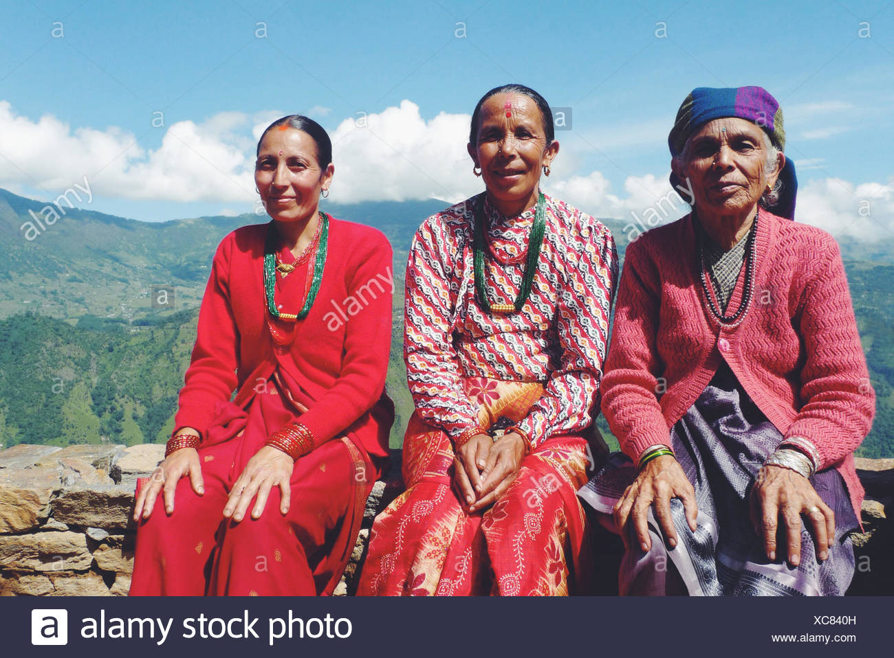 Nepal, Portrait of women sitting on stone wall in mountains - Stock Image