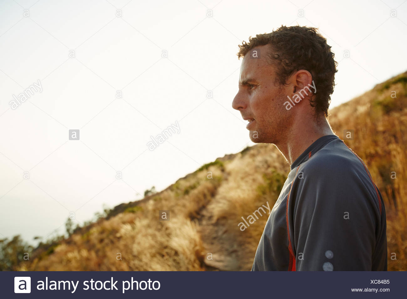 Tired runner taking a break looking away on trail - Stock Image