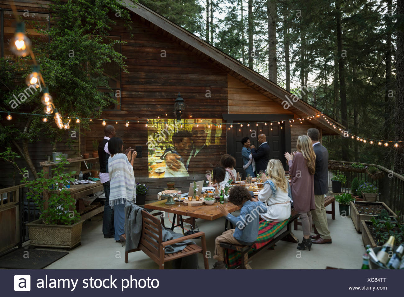 Family and friends celebrating anniversary party watching projected slideshow on cabin balcony - Stock Image