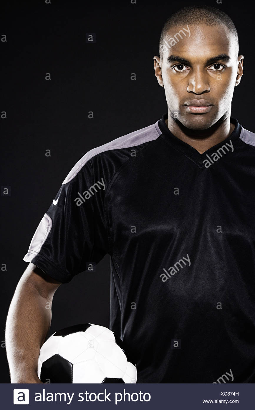 Serious footballer holding a ball - Stock Image