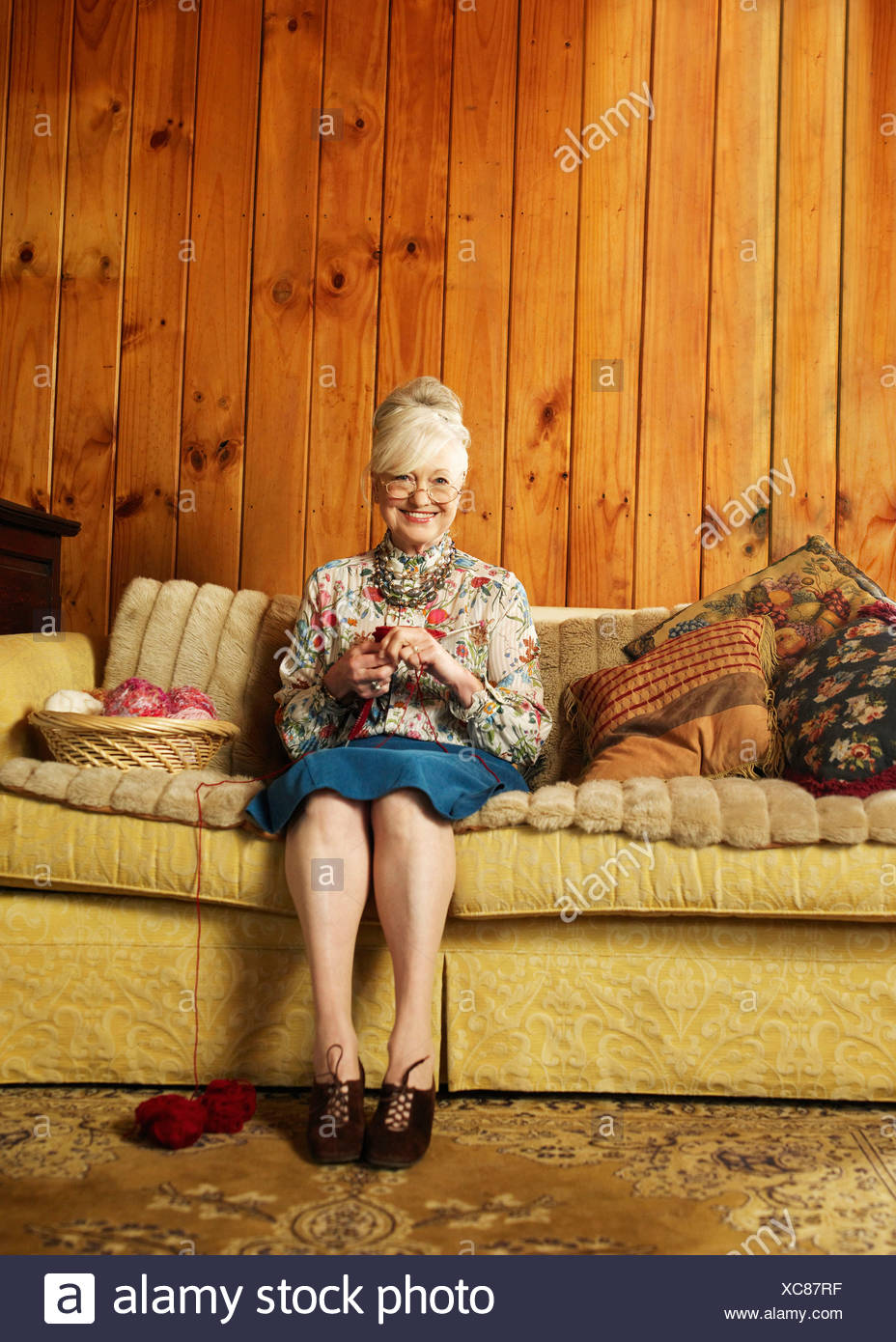 Portrait of happy senior woman knitting on sofa at home - Stock Image