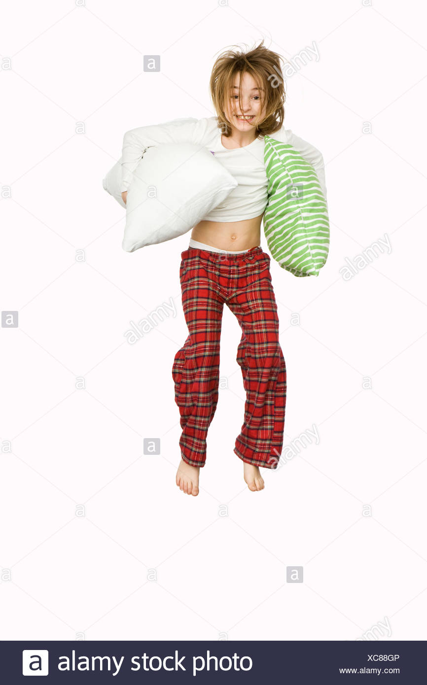 A girl wearing a pajamas and playing with pillows. - Stock Image