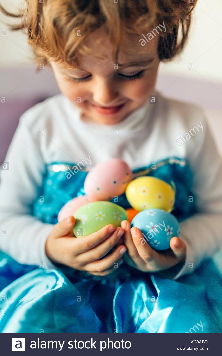 Happy little girl holding Easter eggs - Stock Image