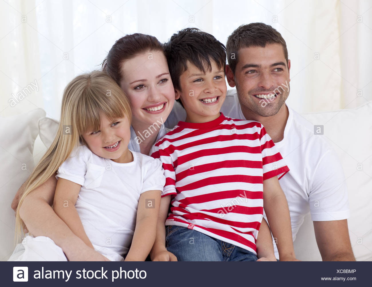 Happy family sitting on sofa together - Stock Image