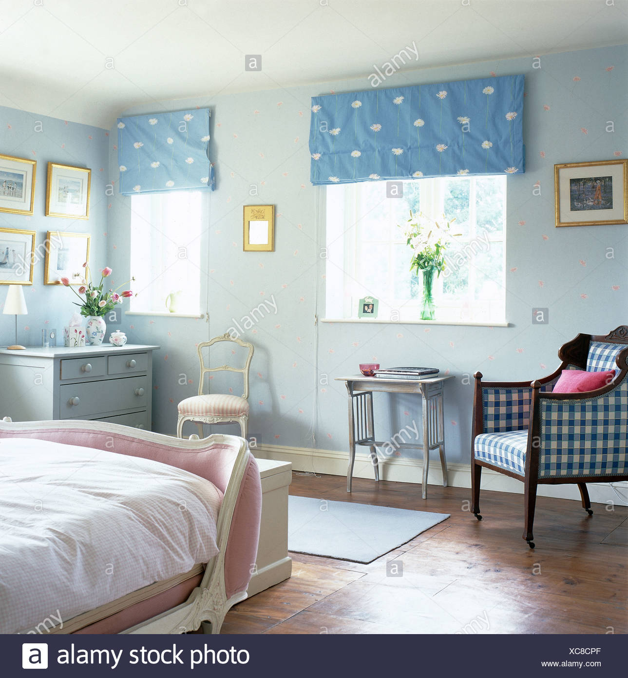 Blue Spotted Blinds On Windows In Pale Country Bedroom With Checked Armchair And Pink