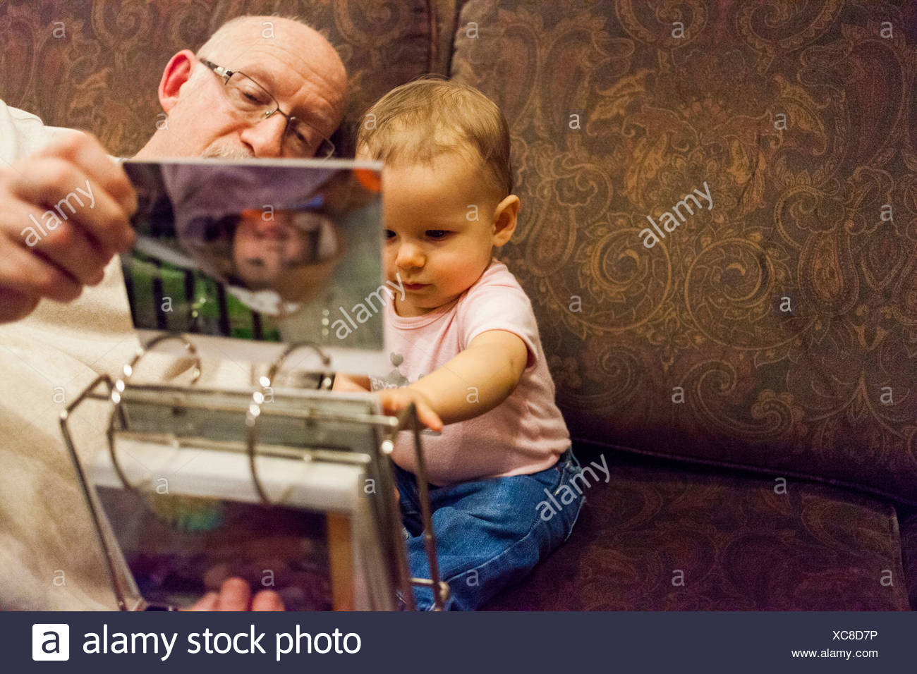 Grandfather and baby granddaughter looking at photo album - Stock Image