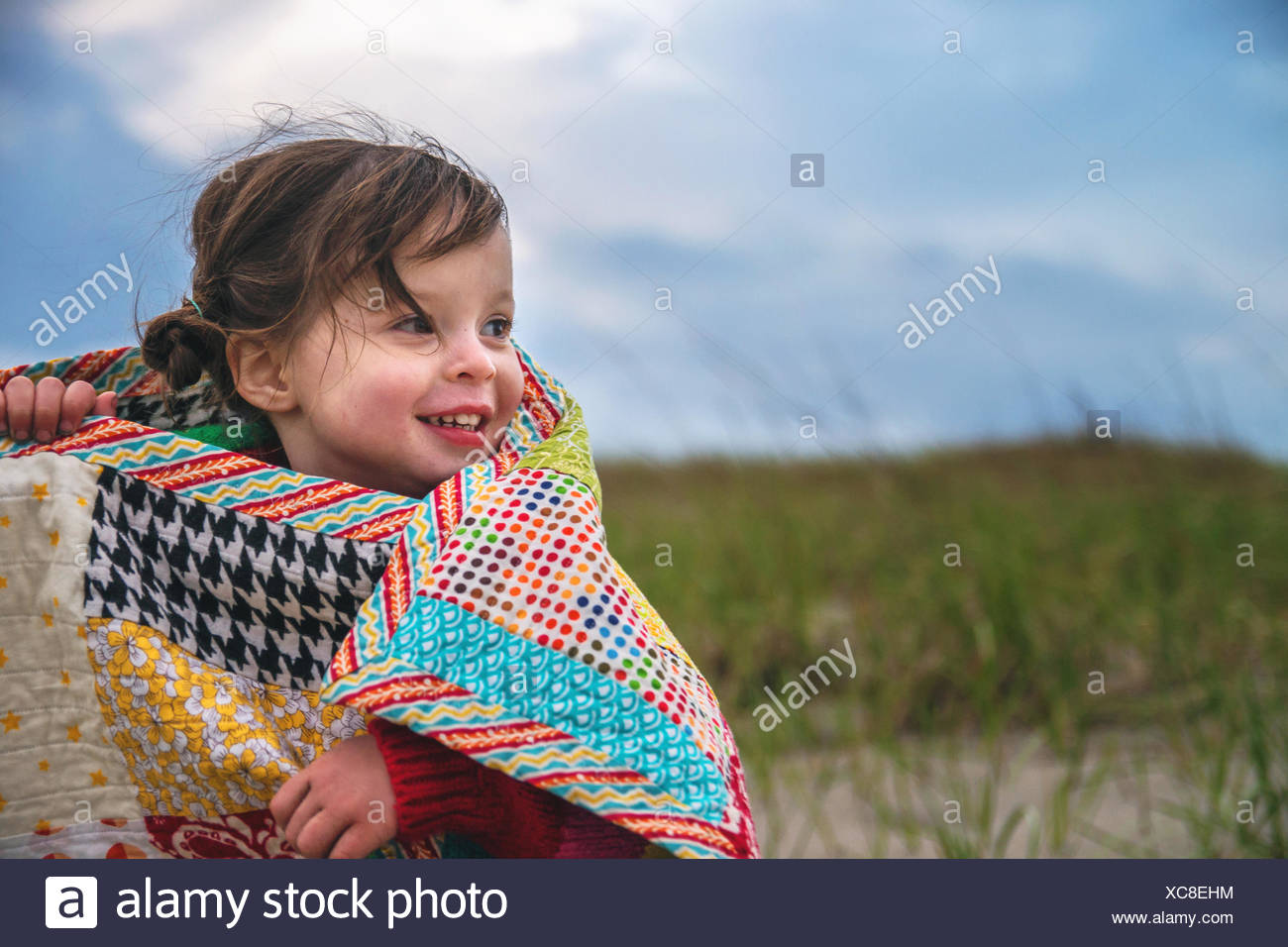 Smiling girl wrapped in a blanket outdoors - Stock Image