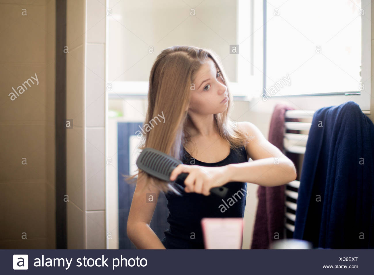 Teenage girl getting hair care with brush - Stock Image