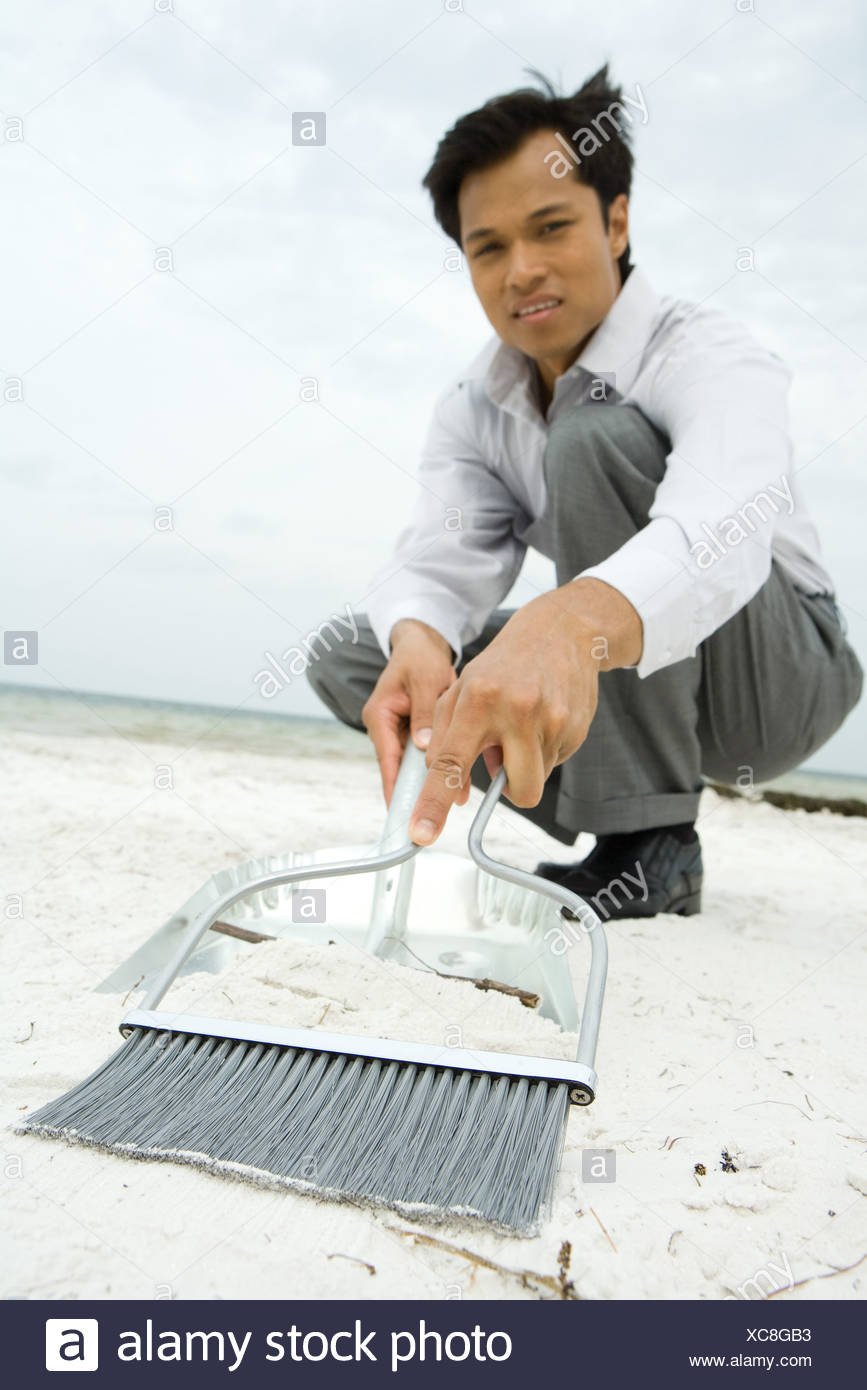 Man crouching on beach, sweeping sand into dustpan, looking at camera, low angle view - Stock Image