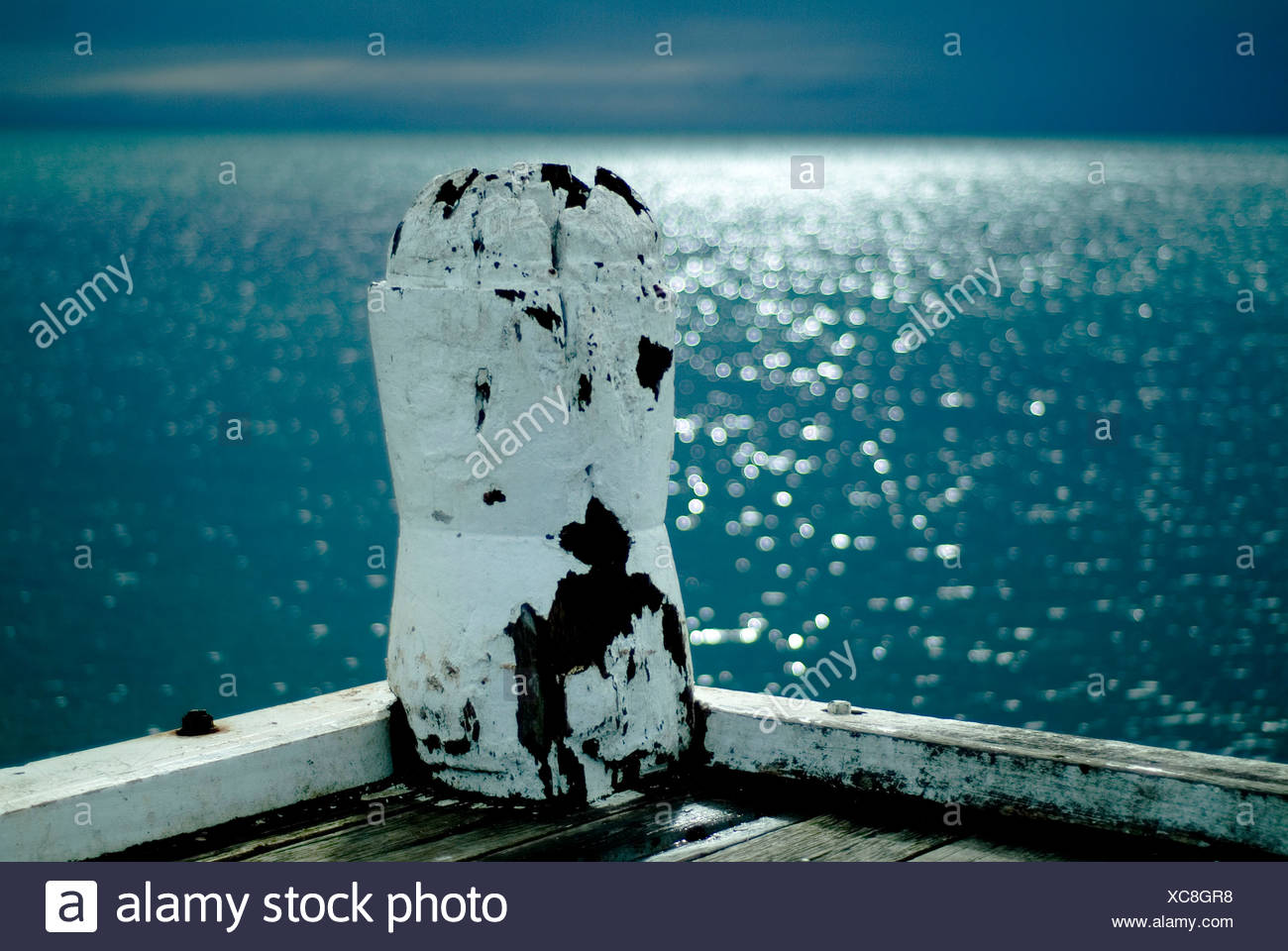 A wooden post pianted white with sparkling blue sea in the distance - Stock Image