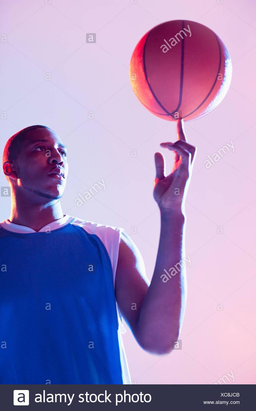 Basketball player balancing ball on one finger - Stock Image