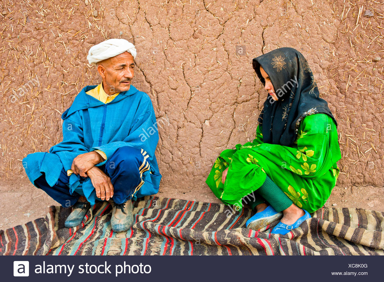 Elderly man and a young girl, Berber people, squatting on a carpet or rug in front of a mud brick house talking - Stock Image