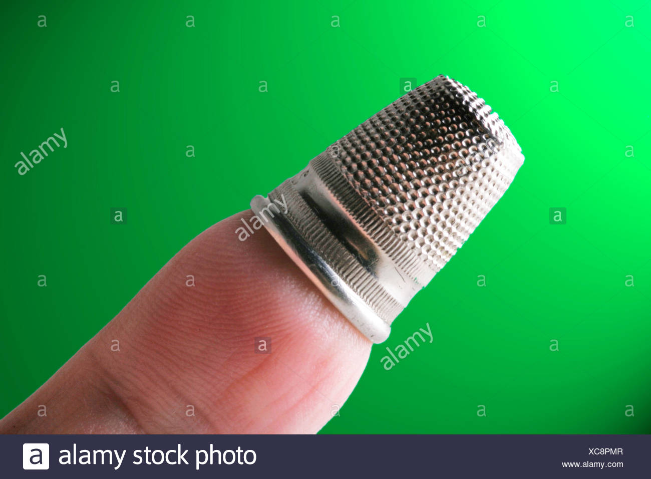 silvery thimble on a finger - Stock Image