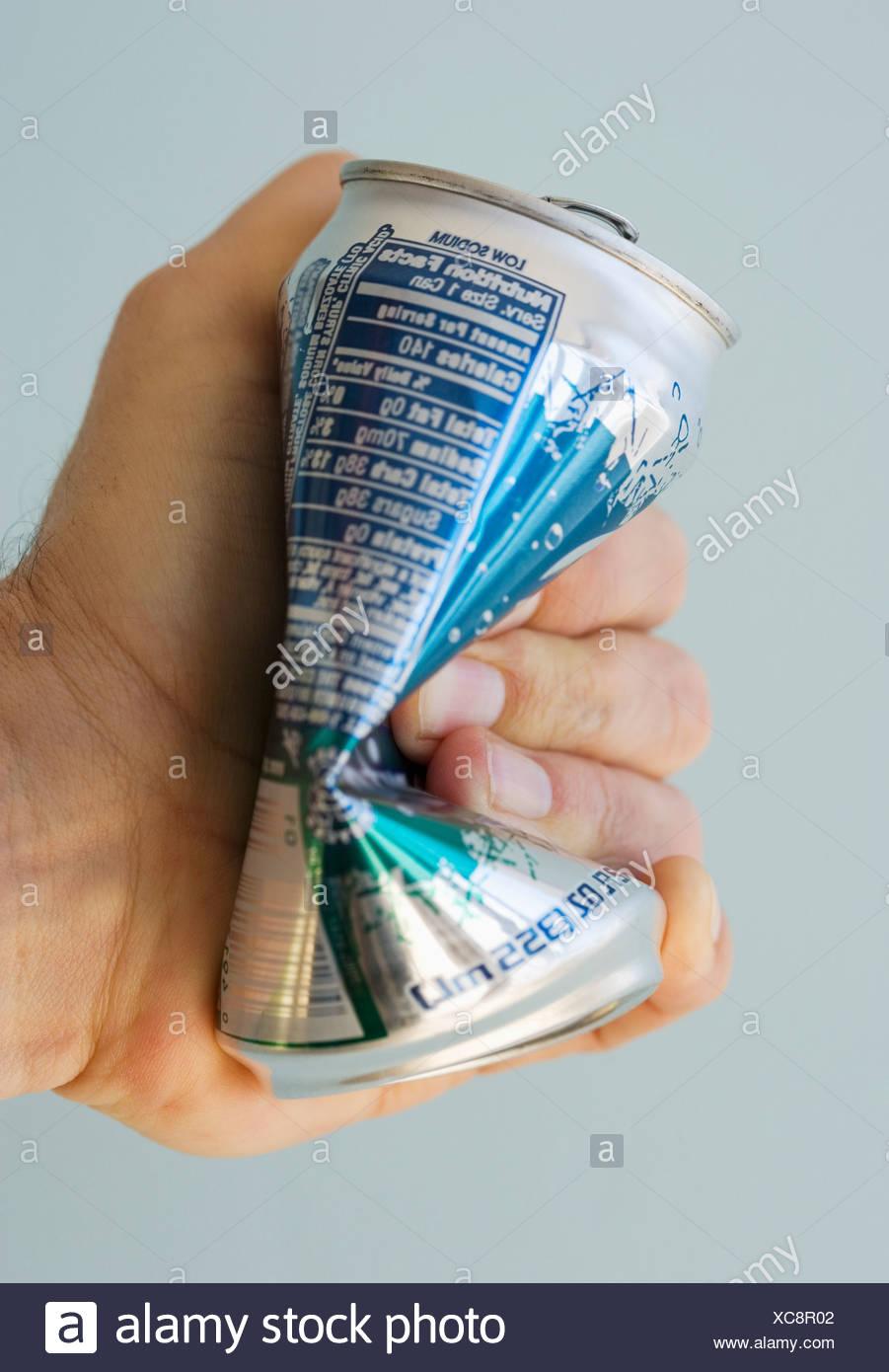 Man crushing tin can - Stock Image