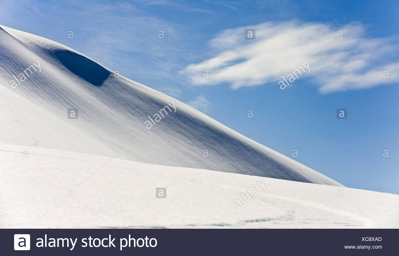 Thin clouds drift over the snow covered eastern slope of Mt. Hawthorne near Juneau, Alaska - Stock Image