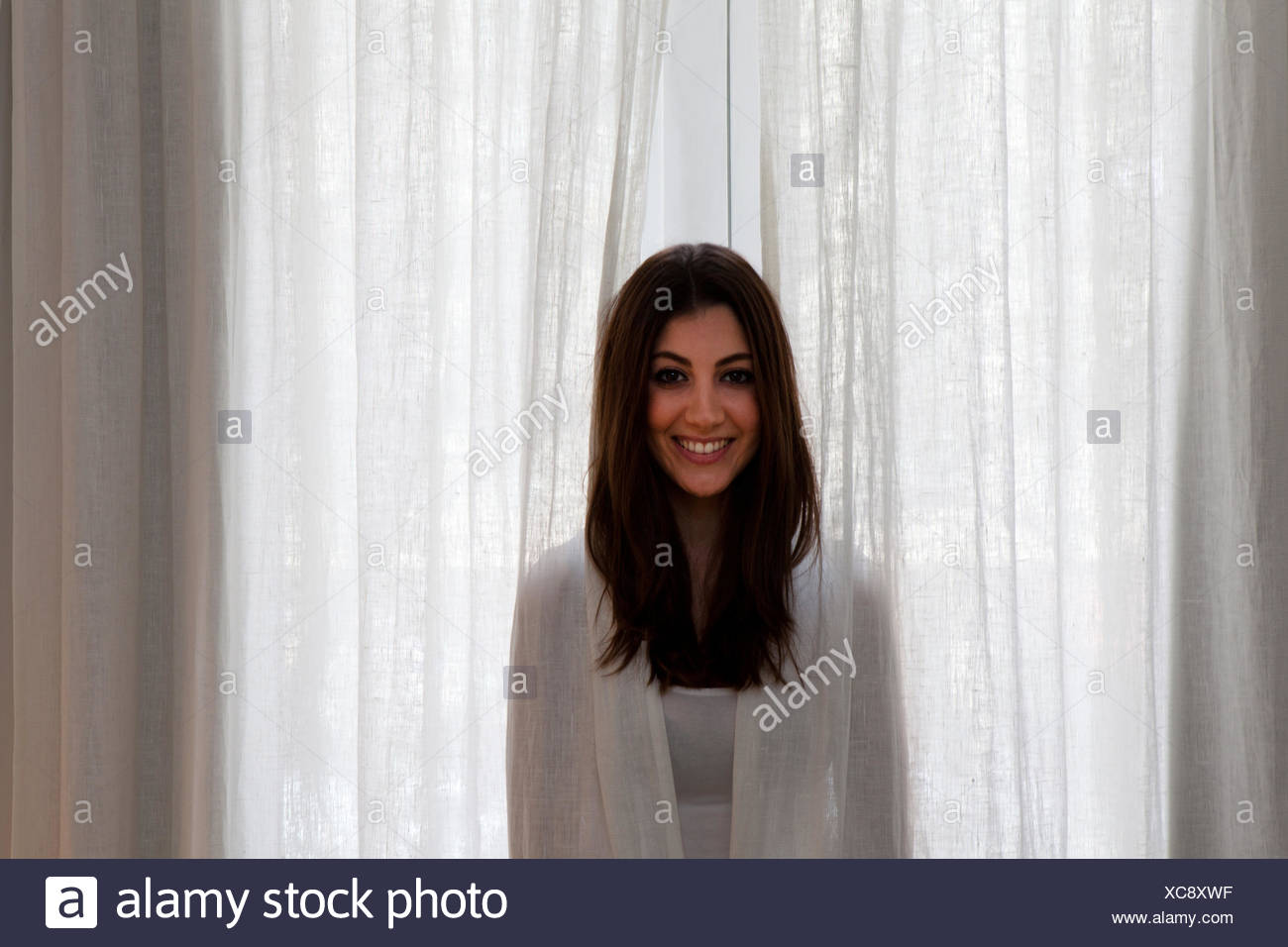 Young adult woman poking head out of curtains - Stock Image