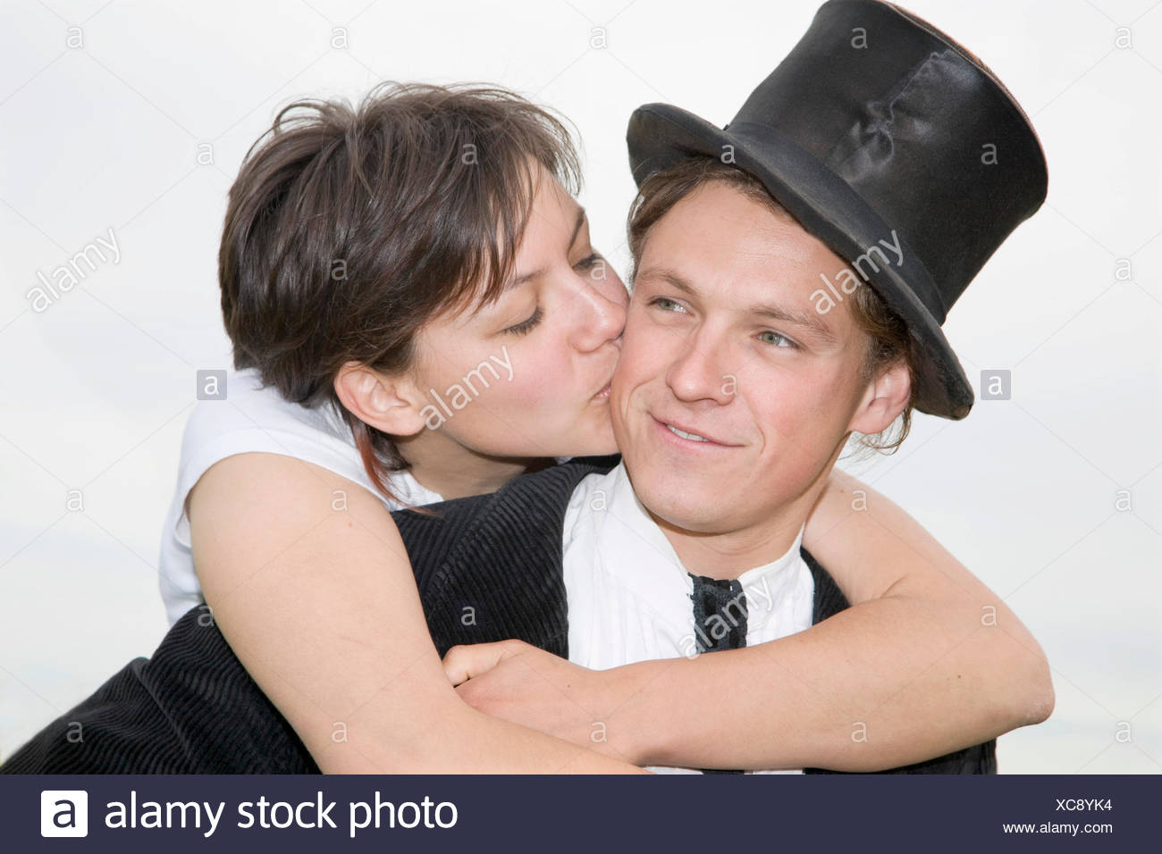 Young man wearing a top hat being tenderly kissed by his partner as he carries her piggyback - Stock Image
