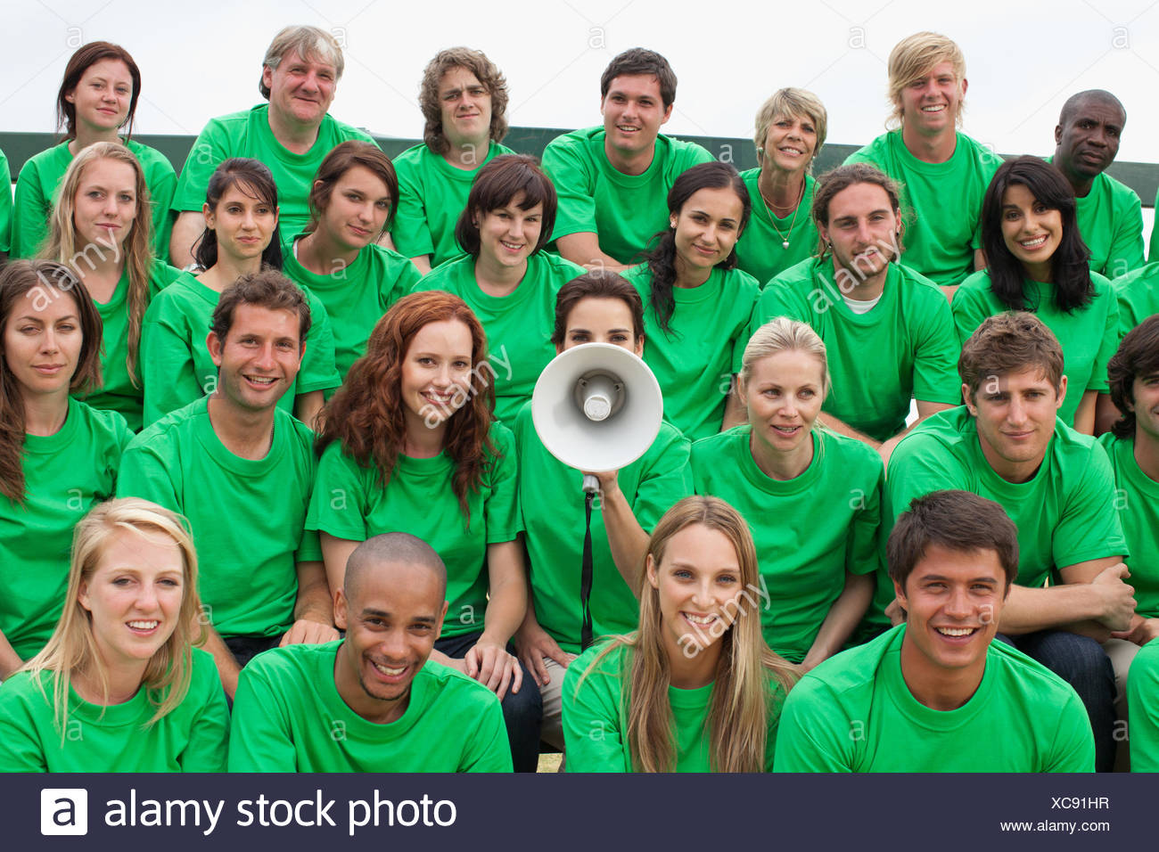 Group of spectators, one person using megaphone - Stock Image